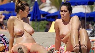 Duas mulheres na praia fazendo topless